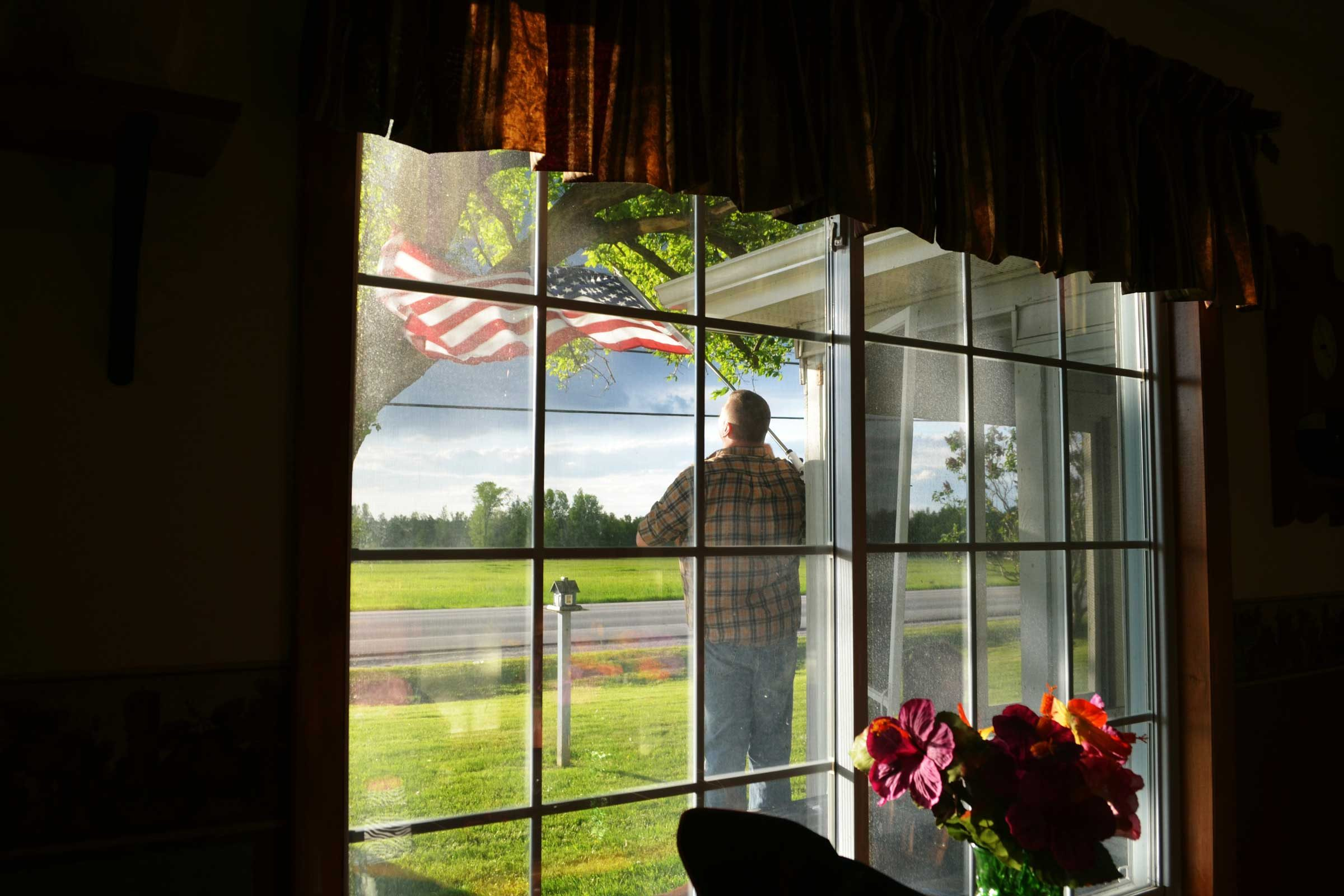 outside a window, a man stands admiring an american flag in the sunlight after a storm