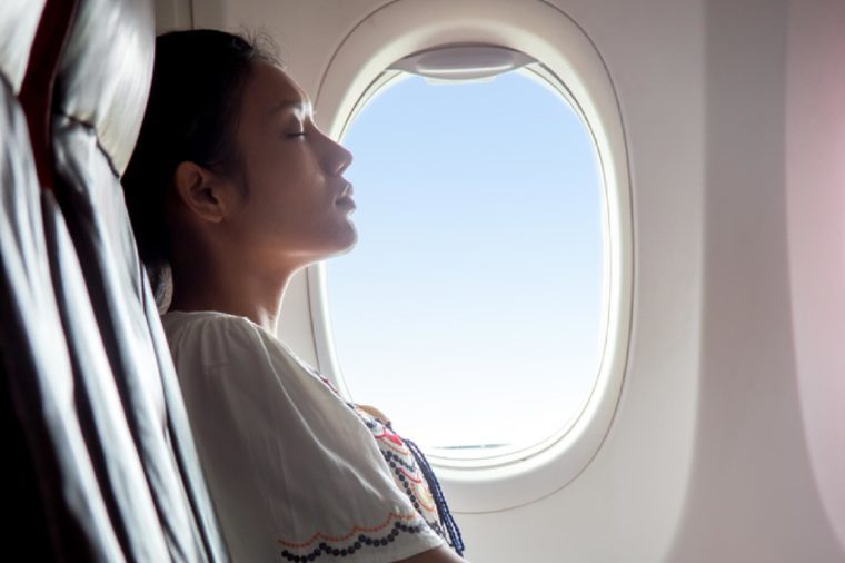 Woman sleeping in an airplane. Passenger in a flying aircraft sleep next to the window. Dreaming traveler beside a window plane with the blue.