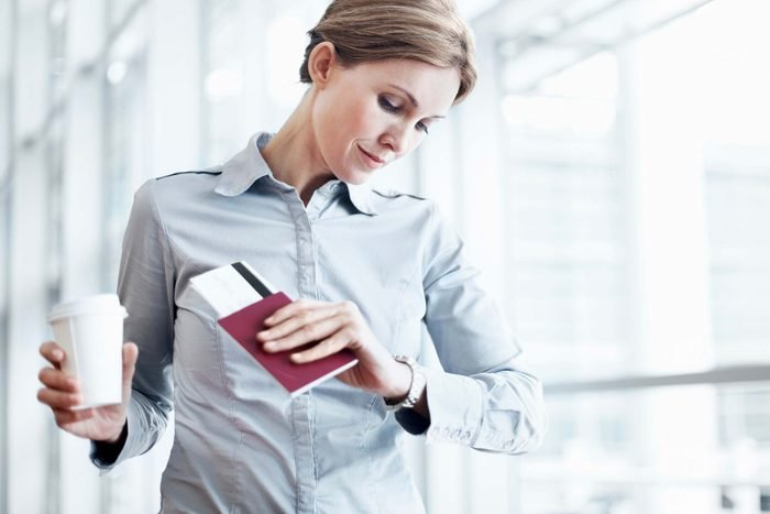 Airplane travel tip woman with coffee and boarding pass
