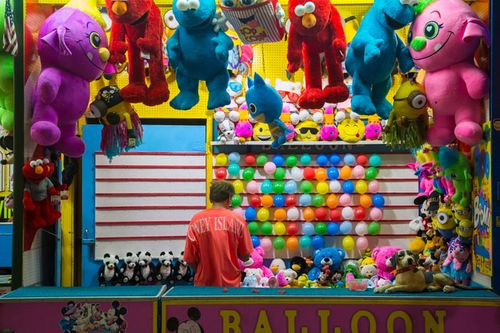 NEW YORK CITY - AUGUST 15, 2017: A worker stands in a balloon-popping booth at the Coney Island boardwalk amusement park.