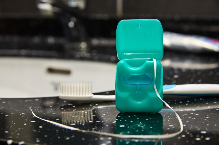 Dental floss with opened lid on a background of washstand