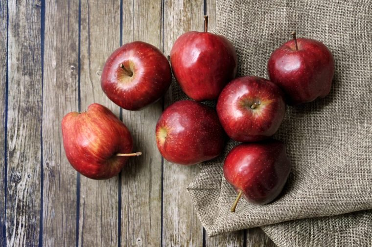 A group of fresh red apple on the wooden table with vintage sack