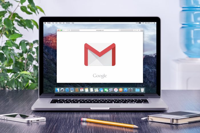 Google Gmail logo on the Apple MacBook Pro display that is on office desk workplace