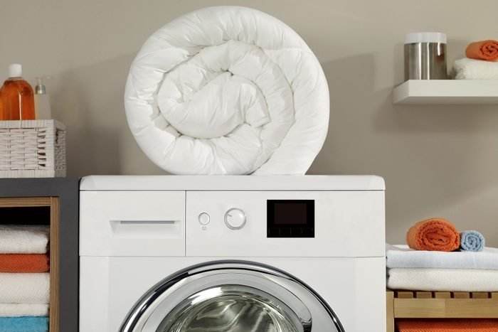 down comforter on top of a washing machine in laundry room