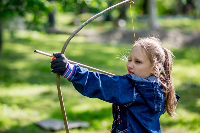 Russia, Vladivostok, 05/27/2017. Young girl shoots from home-made wooden archery bow