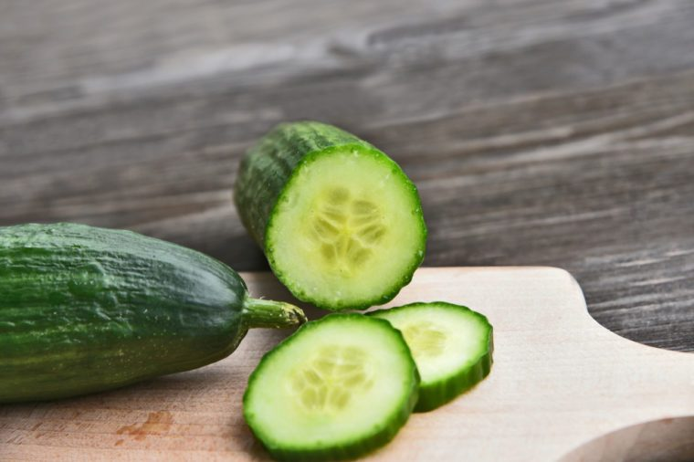 Cucumber seeds are edible and very nutritious. Fresh Cucumber slice on wooden board with wooden background.