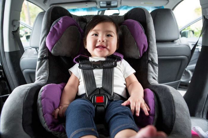happy child in a rear facing car seat in the back seat of a car