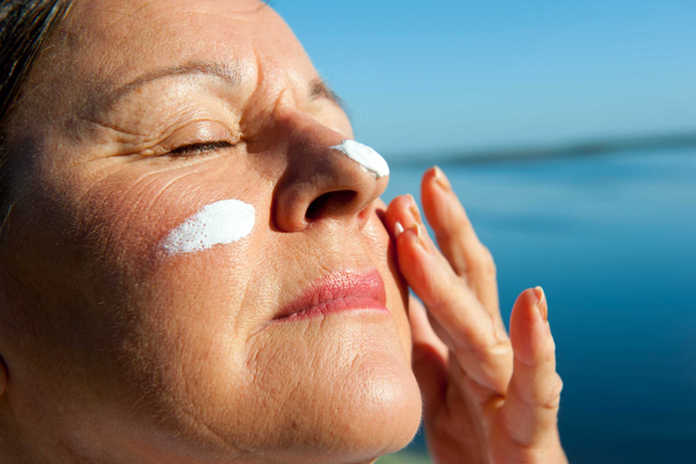 woman applying sunscreen on her face