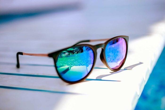sunglasses on the edge of a pool