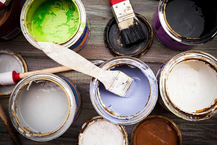 overhead view of open cans of paint with paint brushes