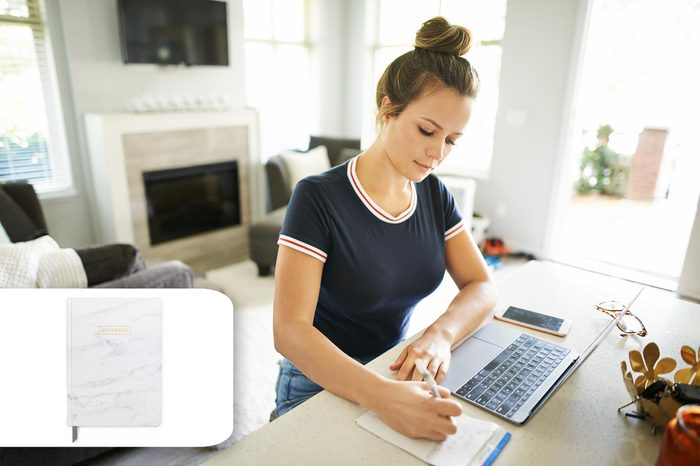 woman sitting at the counter with computer and a notebook. target notebook.
