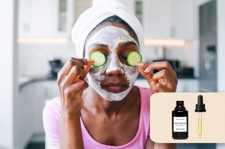 woman at home with a face mask, hair towel, and cucumbers over her eyes. town and anchor face serum.