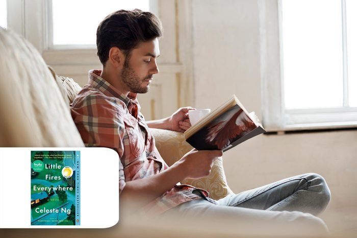 man on his couch reading a book. target book little fires everywhere.
