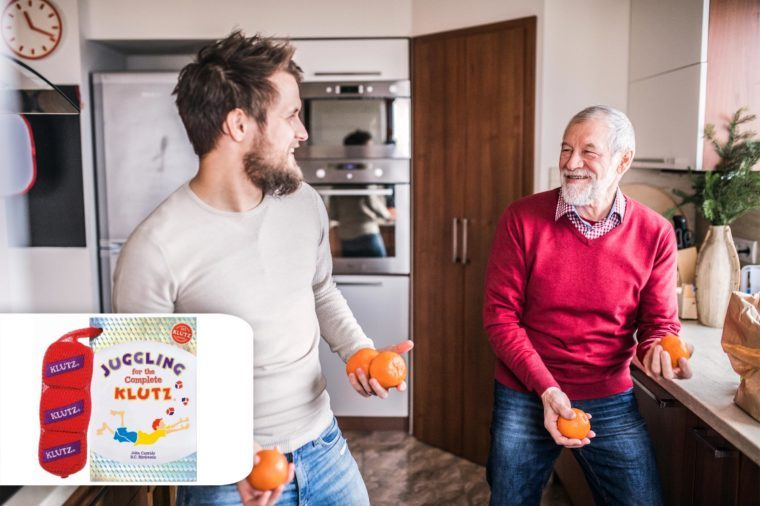 two men, adult grandson and grandfather, in the kitchen juggling with oranges. target klutz juggling set.