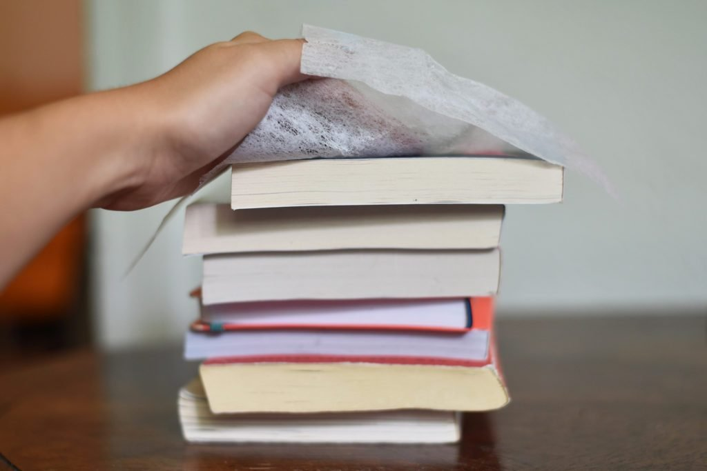 hand using a dryer sheet to clean a stack of old books