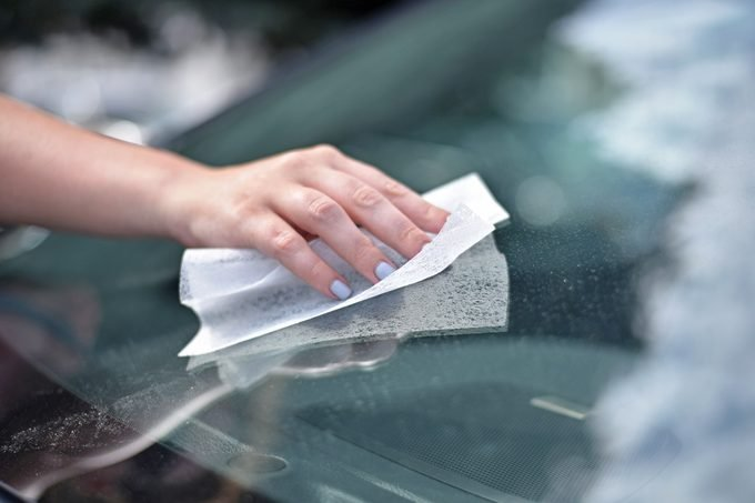 hand using a dryer sheet to clean a bug off a car windshield