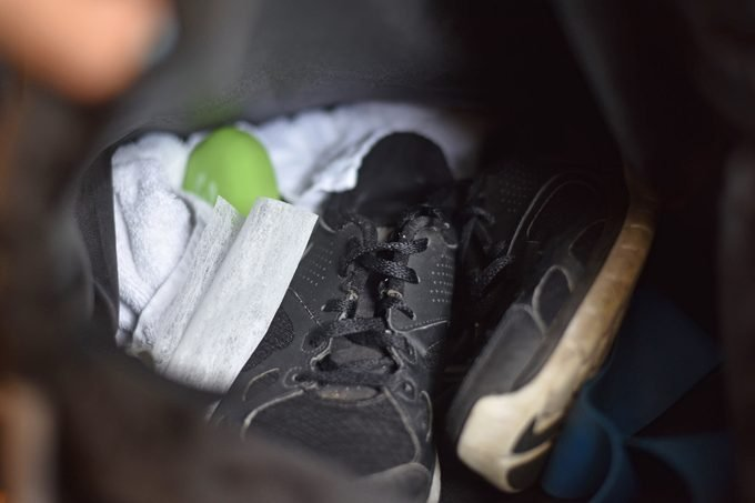 open gym bag with sneakers, a towel, and a dryer sheet
