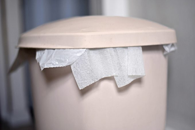 closed trash can with dryer sheets sticking out from under the lid