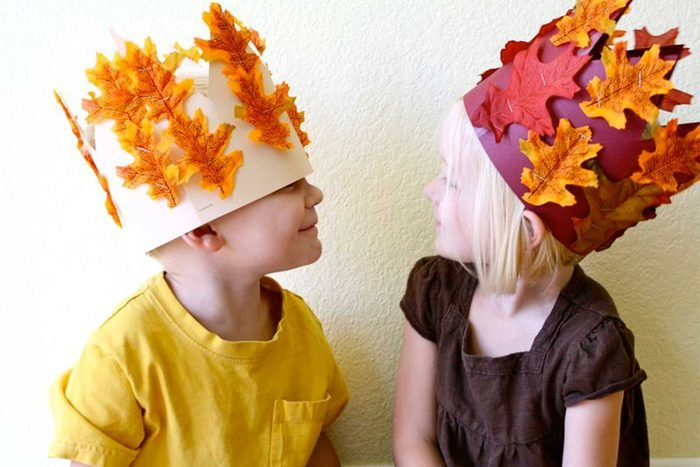 kids wearing harvest crowns they made for thanksgiving