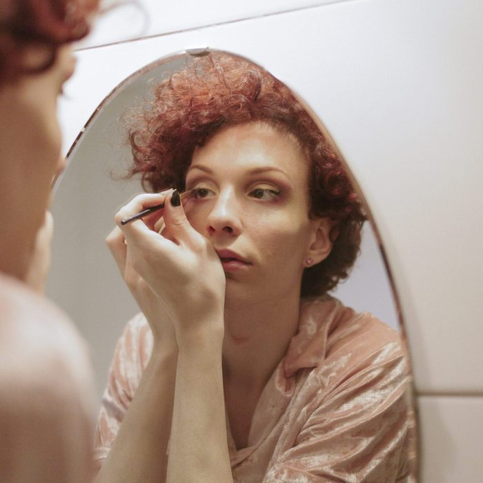 Woman with red hair applying makeup in mirror