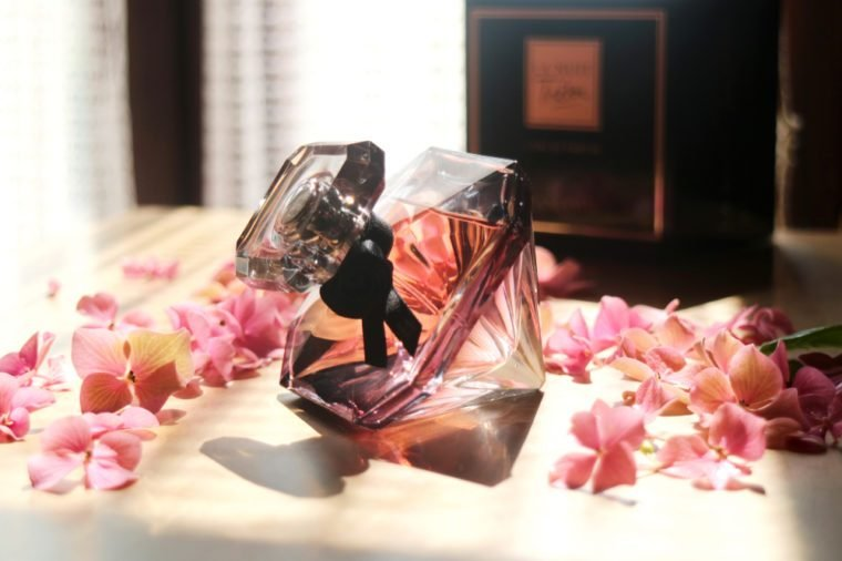 Paris, France: August 18 2018- A bottle of Lancôme La nuit Trésor perfume with ิblowing light and shadow, with petals of pink flowers