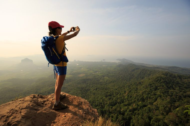 woman hiker taking photo with smartphone on mountain peak