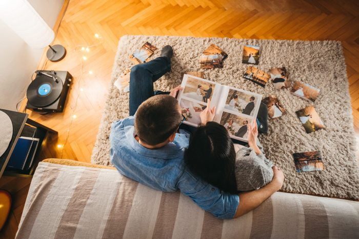 Couple looking at wedding photo album together. overhead view.