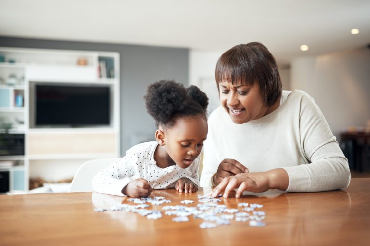 Shot of a little girl building a puzzle with her mother at home
