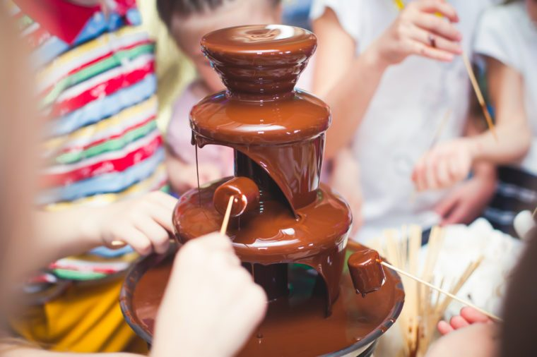 kids dipping marshmallows in a chocolate fountain