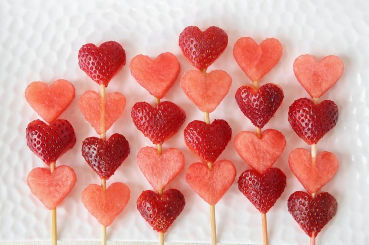 heart shape strawberry and watermelon fruit skewers on white plate, fun food art for Valentines day