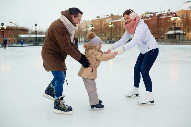 Young parents teaching their daughter to skate