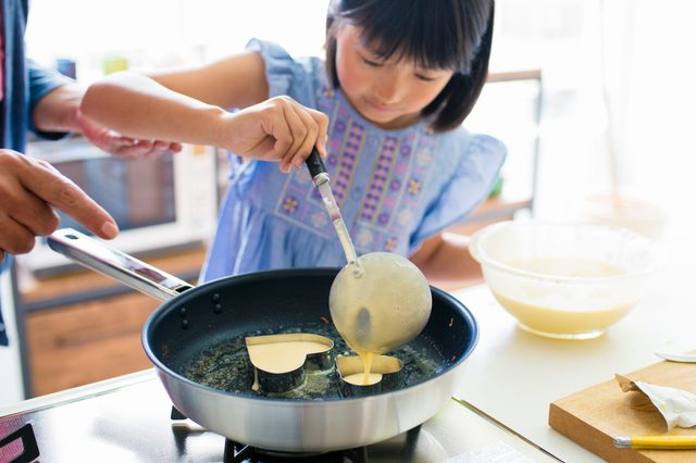young girl making heart shaped pancakes with the guidance of an adult out of frame