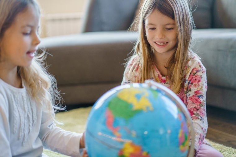 Two cute sisters sitting and looking at globe