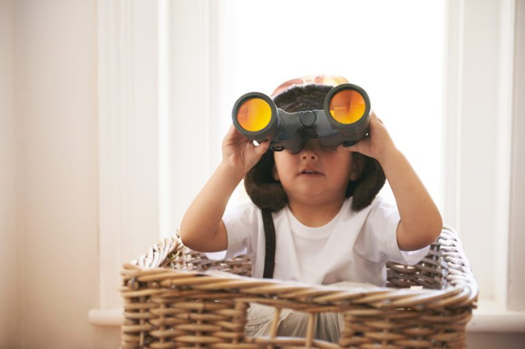 A little boy sitting in a basket looking through binoculars
