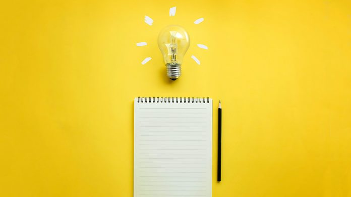lightbulb, notebook, and pencil on yellow background. writing will make you smarter. note taking concept.