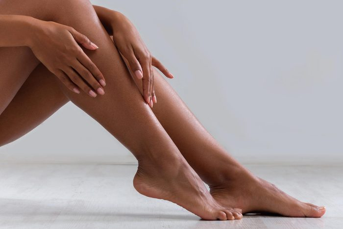 woman rubbing in lotion on legs and feet