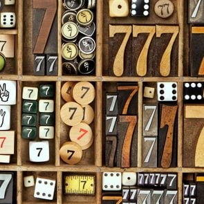 a collection many wooden number sevens and lucky dice in a letterpress drawer