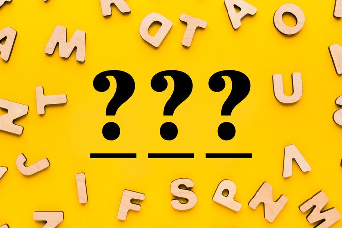 scattered wooden letters on a yellow background with three question marks over three blanks in the center
