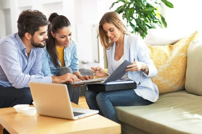 Real Estate agent offer home ownership and life insurance to young couple.