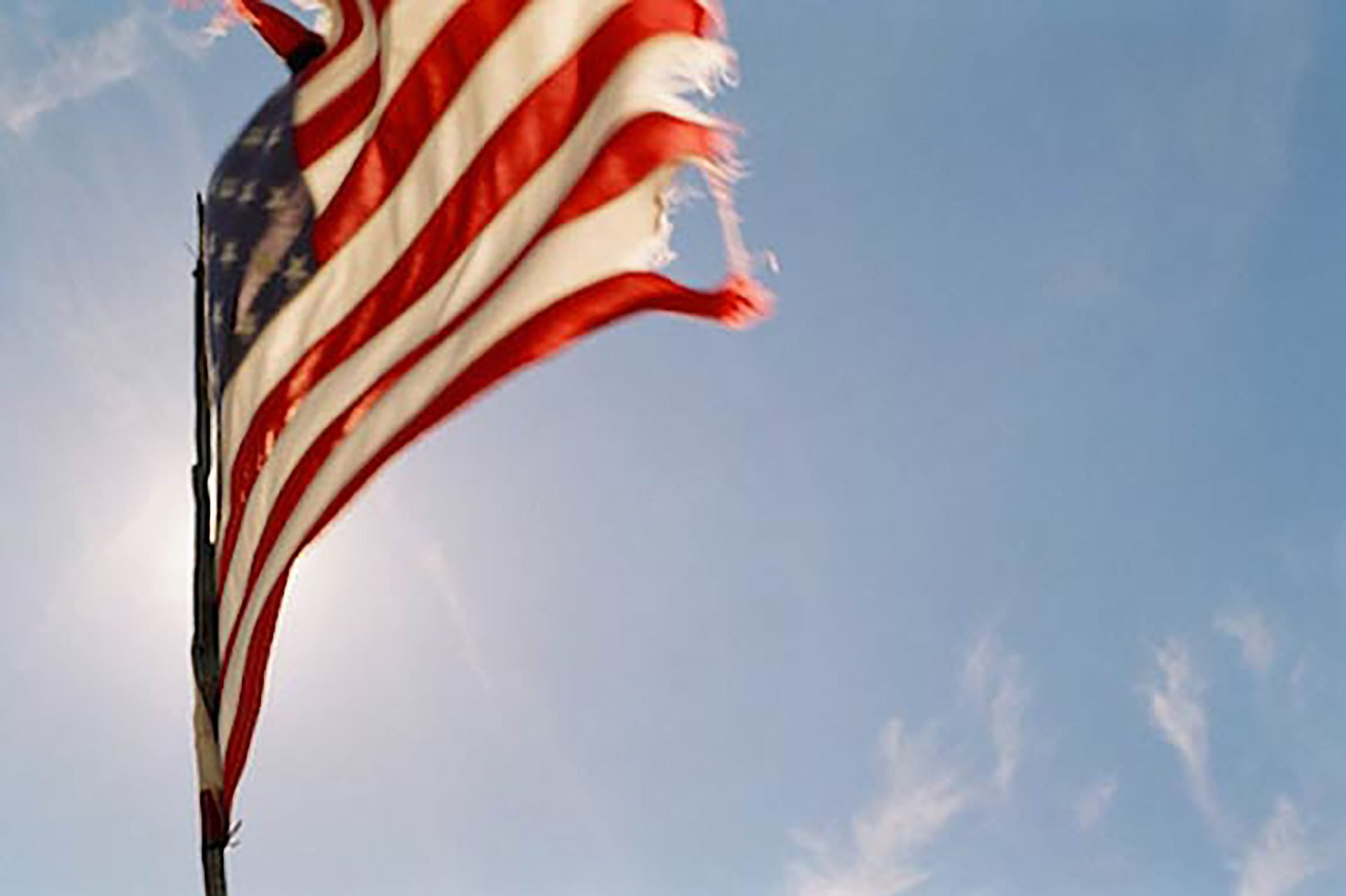 a wind tattered american flag lit from behind by the sun waves vibrantly against the blue of the sky