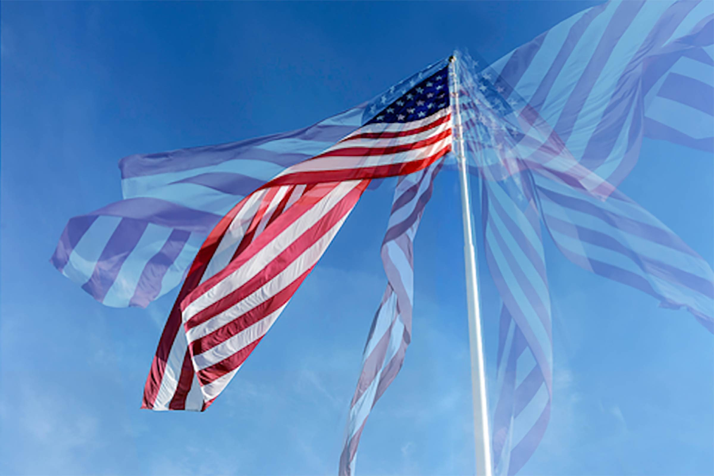 a multiple exposure image of an american flag waving against a blue sky