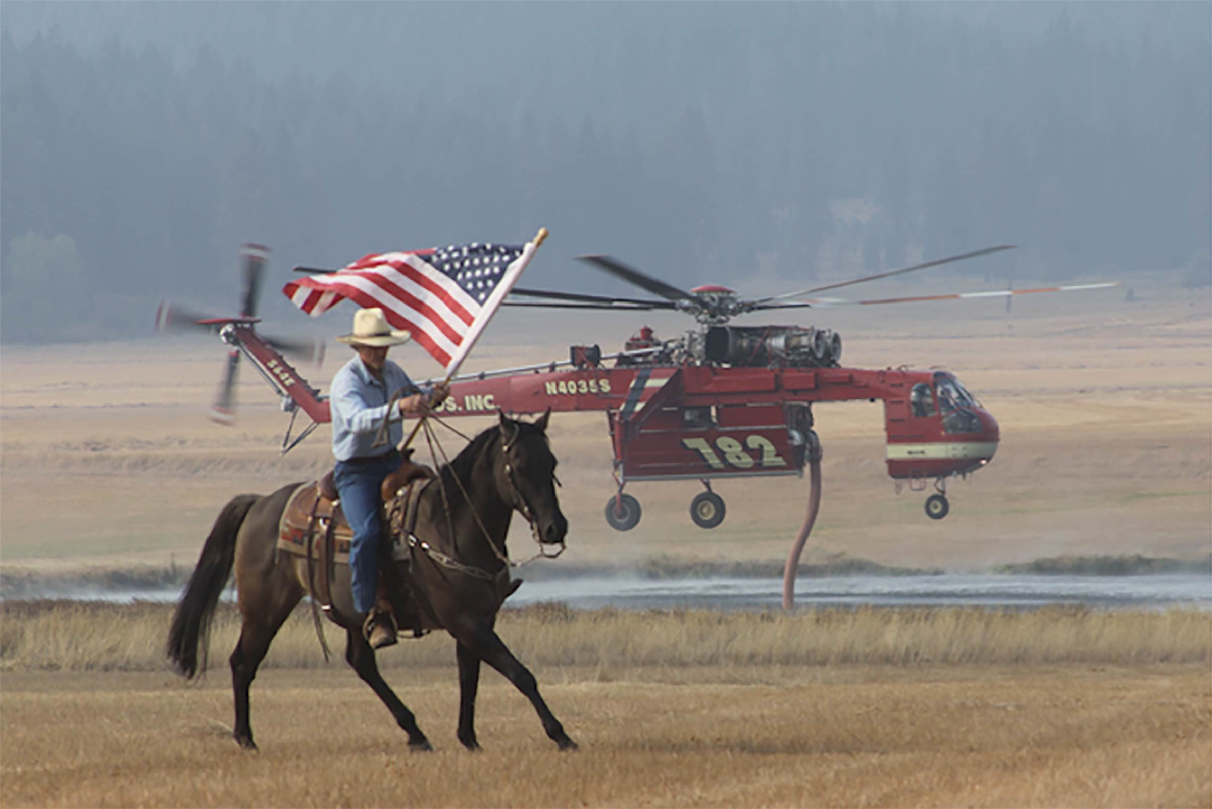 a man on a horse waves an american flag to show support for the fire department helicopter in the background