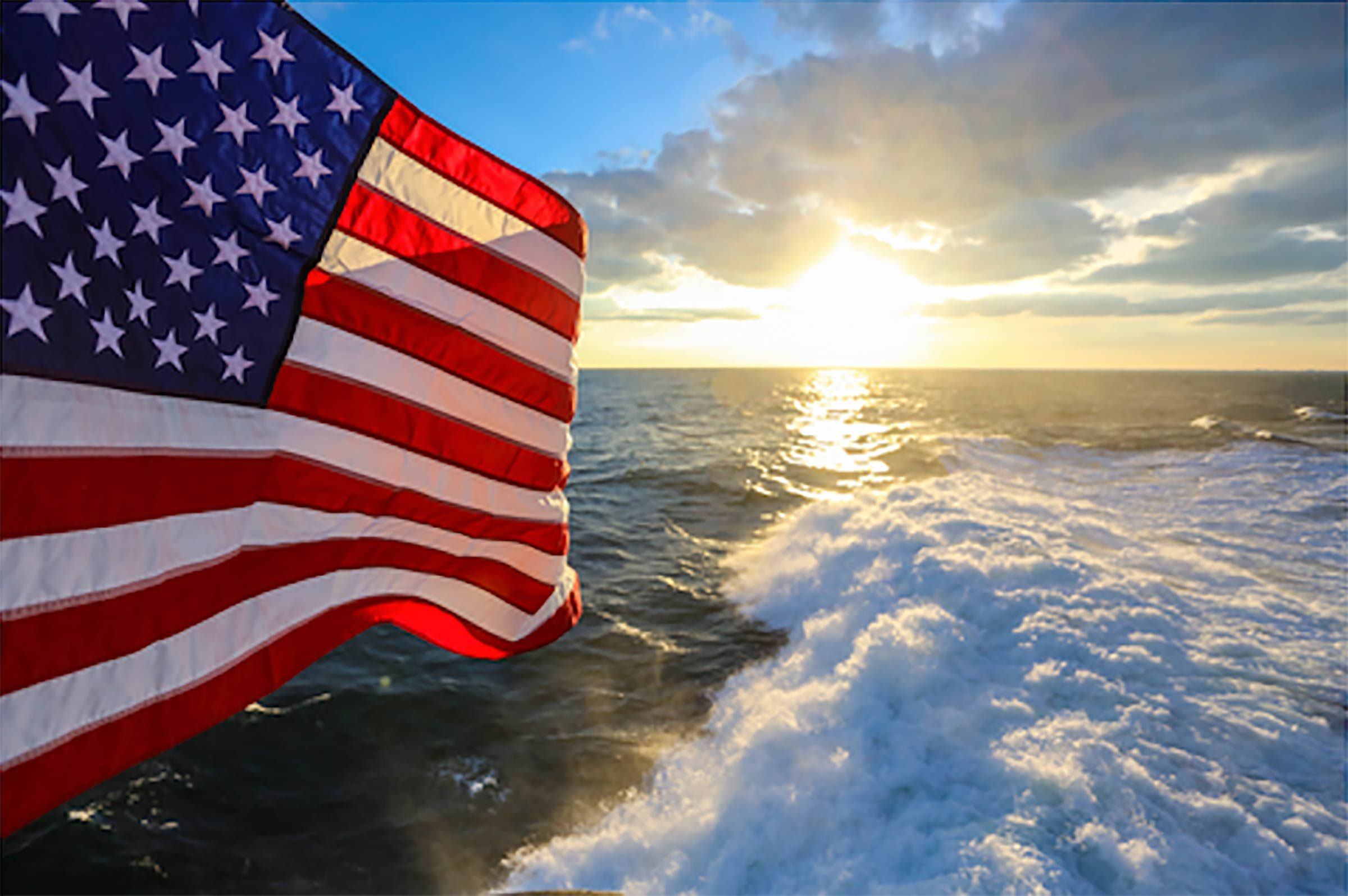 view of the sun, an american flag, and the Atlantic Ocean from the top of the sail of the USS Norfolk