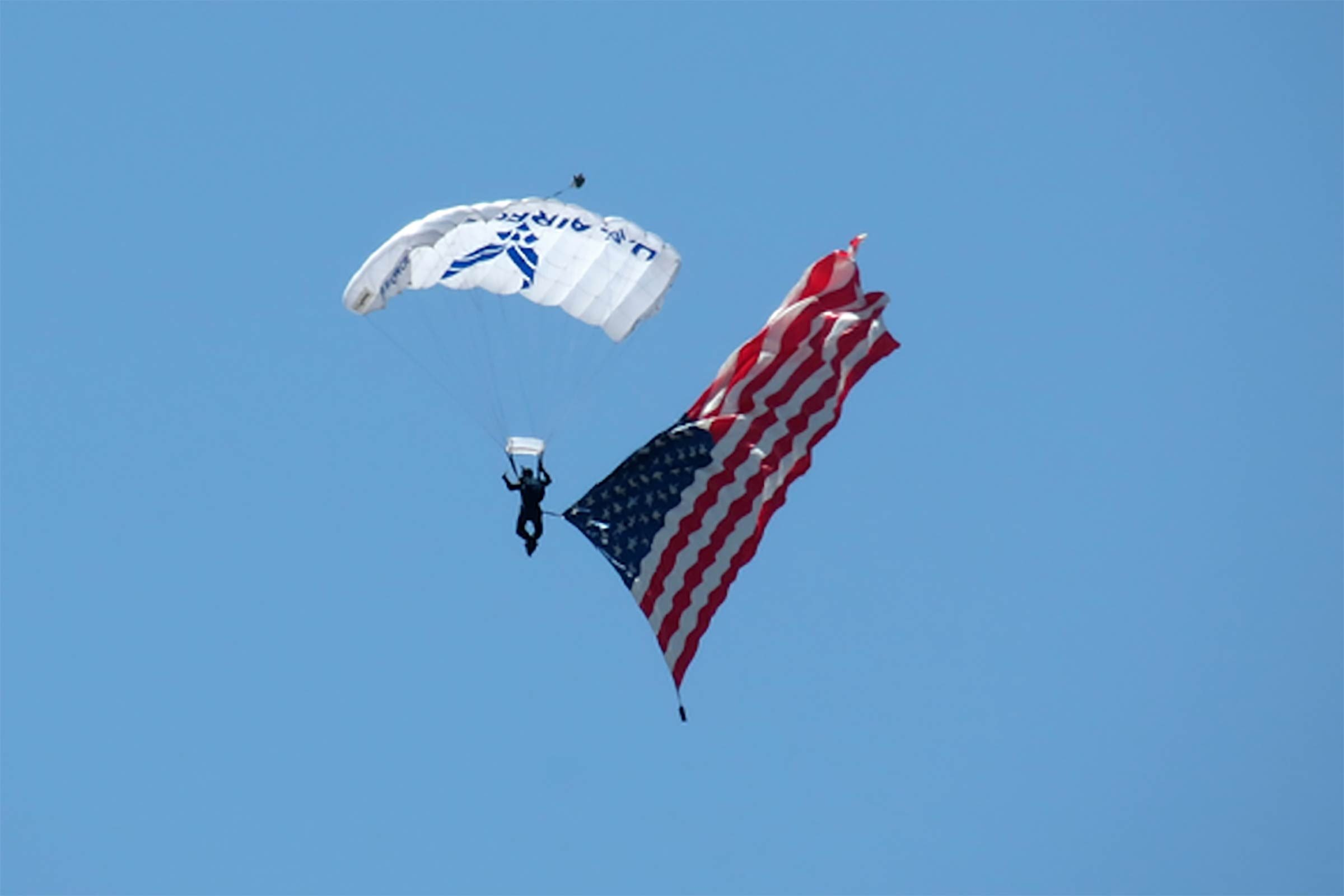 a member of the U.S. Air Force Academy Wings of Blue precision parachute team floats through the clear blue skies above Davis-Monthan Air Force Base in Tuscan, Arizona with an american flag