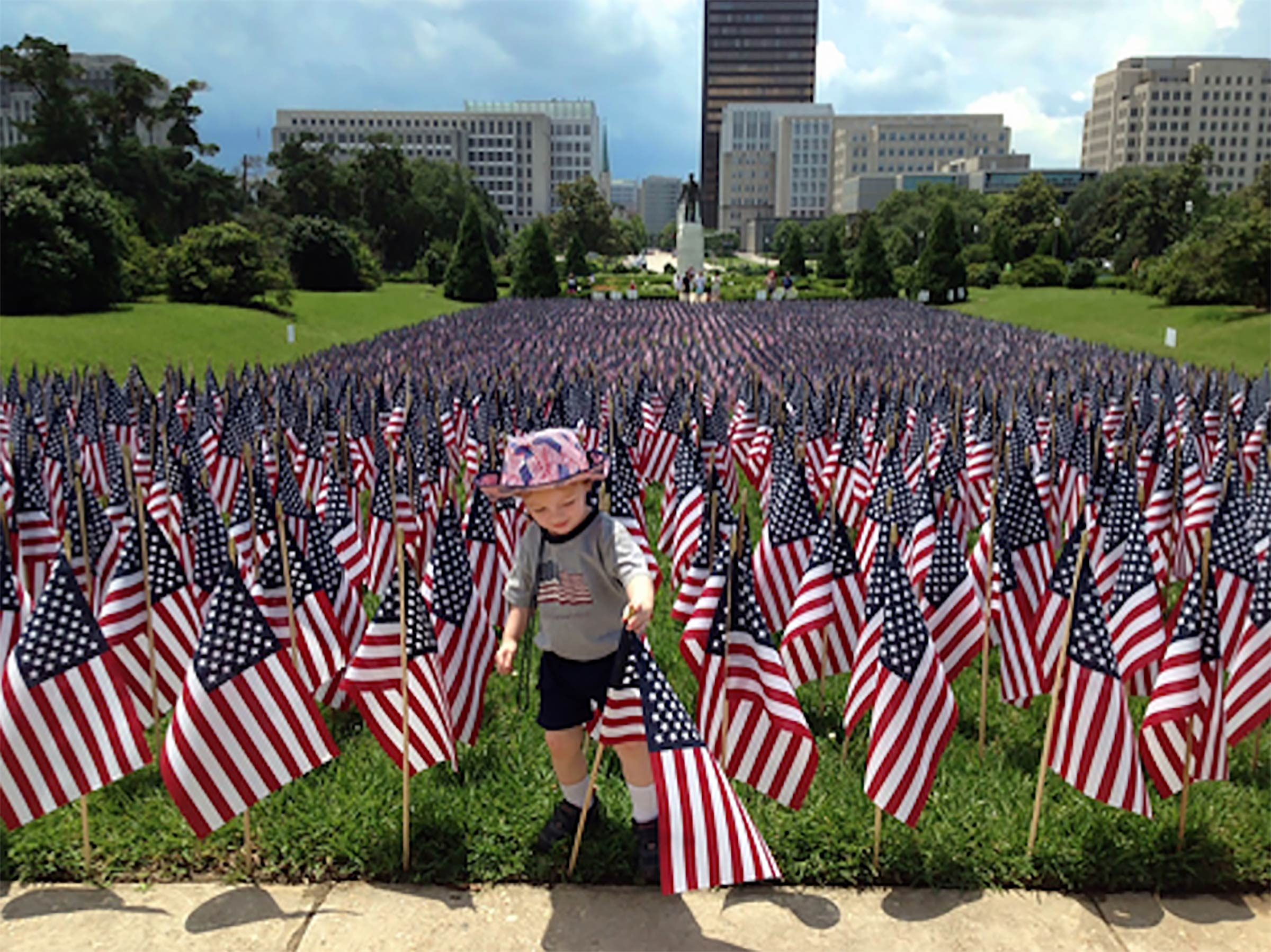 a young boy stands among a field of american flags and reaches to adjust one that is leaning; Zachary, Louisiana