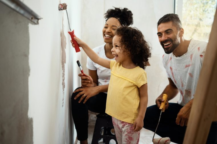 Young family renovating their home, painting wall