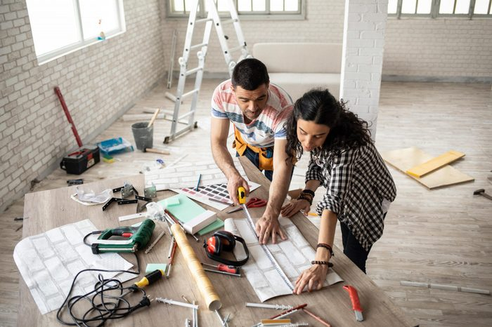 Couple making home improvement, measuring, high angle view.