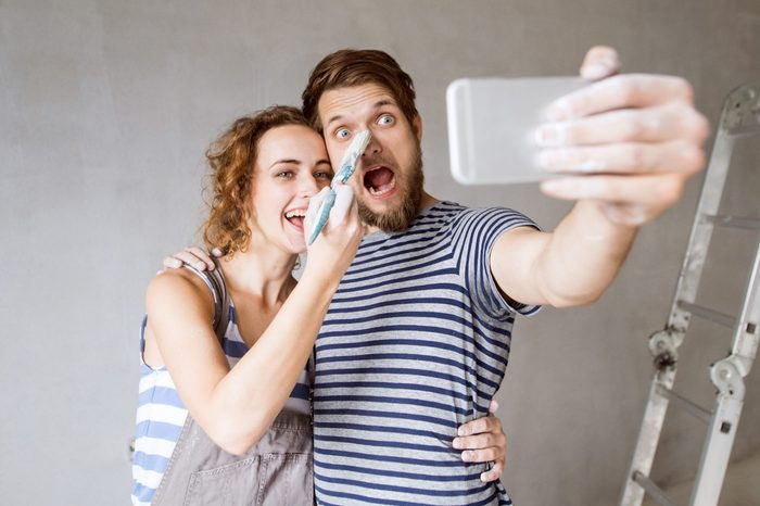 Beautiful young couple in love having fun, painting walls of their new house, taking selfie with smart phone. Home makeover and renovation concept.