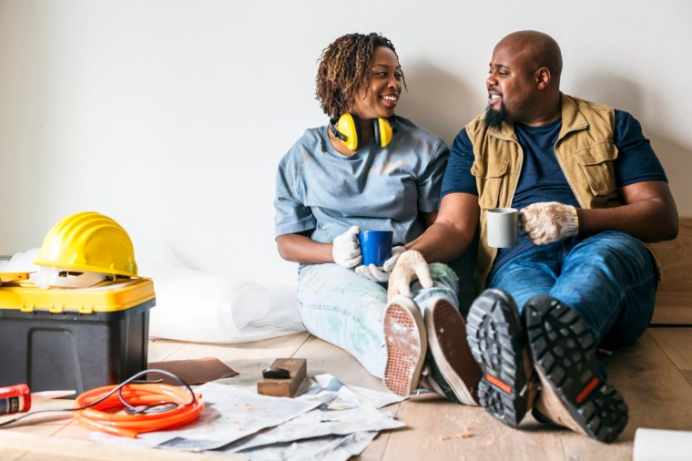 couple taking a break from renovations. smiling at eachother with coffee mugs.