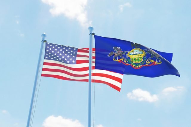 USA and state Pennsylvania, two flags waving against blue sky. 3d image